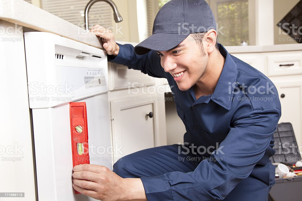 Plumber working on dishwasher in domestic kitchen stock photo
