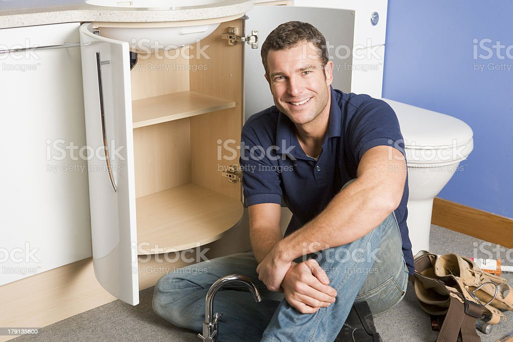 Plumber working on sink and sitting on the floor smiling royalty-free stock photo