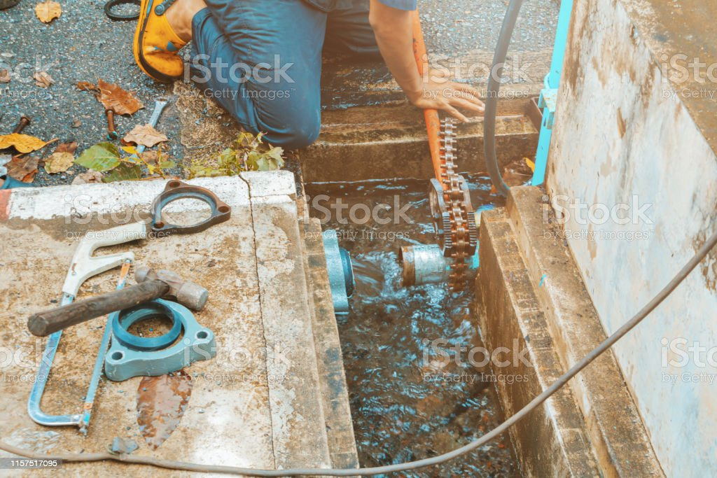 plumber working repair the broken pipe with Adjustable Wrenches or...