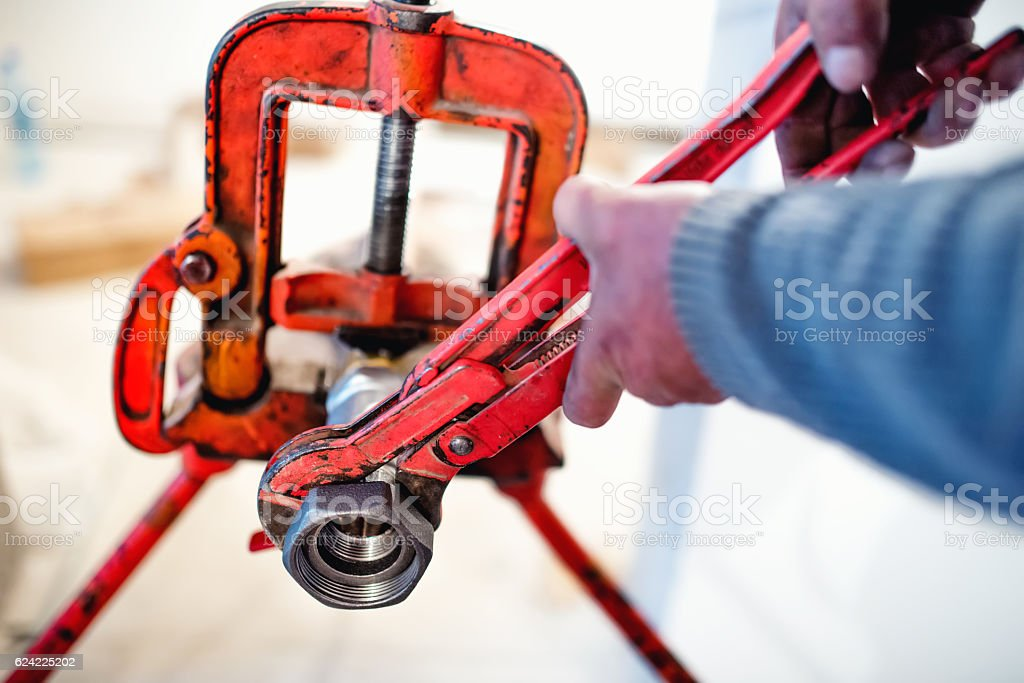 plumber working with wrench and tools stock photo