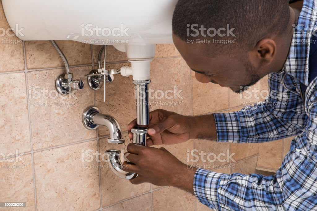 Plumber's Hand Fixing Sink In Bathroom stock photo