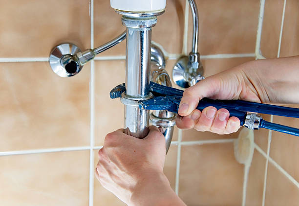 Plumber's hands with a blue wrench working on a sink's pipes stock photo