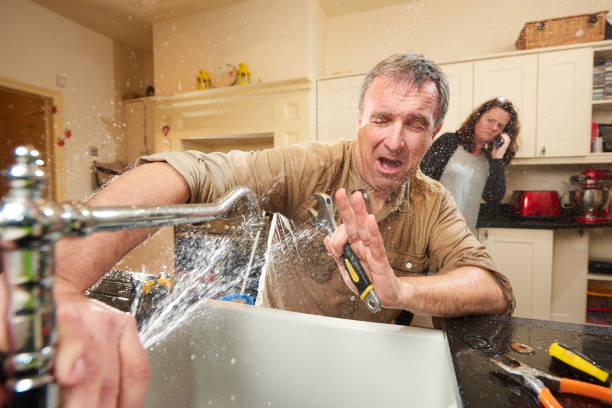 plumbing mishap give it a go DIY hero tries his hand at fixing the tap . His wife is already on the phone to an emergency plumber as water gushes from the broken tap accidents and disasters stock pictures, royalty-free photos & images