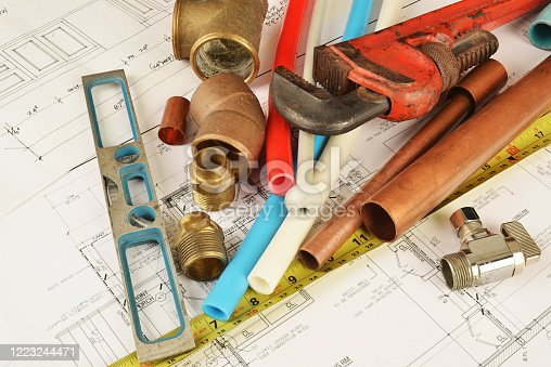 house renovation blueprints with plumbing pipes and tools