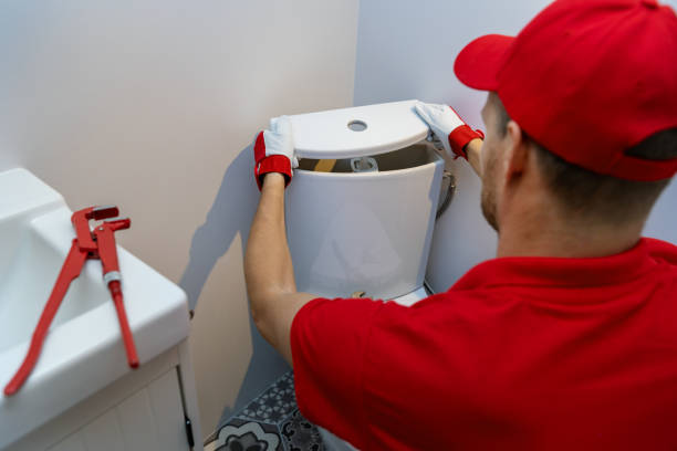 plumbing services - plumber working in bathroom installing toilet wc water tank stock photo