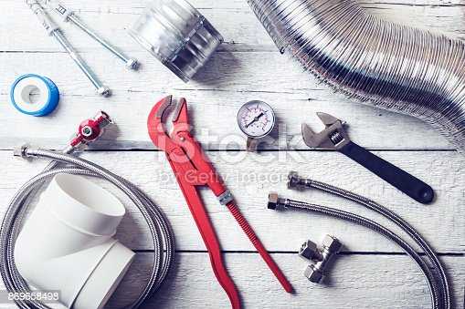 istock plumbing tools and accessories on wooden table. top view 869658498