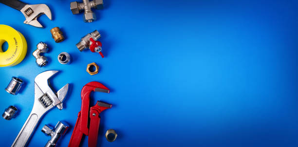 plumbing tools and fittings on blue background with copy space stock photo