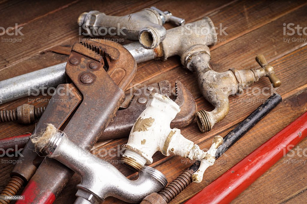 plumbing tools lying with old pipes and faucets stock photo