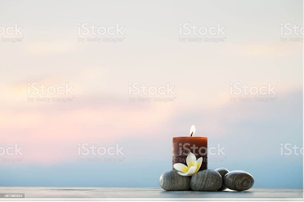 Plumeria flower, candle and stones for spa background stock photo