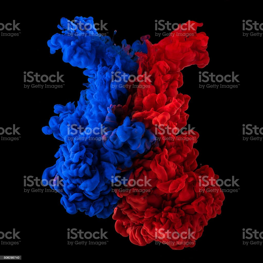 Plumes of red and blue ink in water stock photo