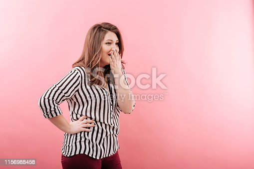 istock Plump female laughing and covering mouth 1156988458
