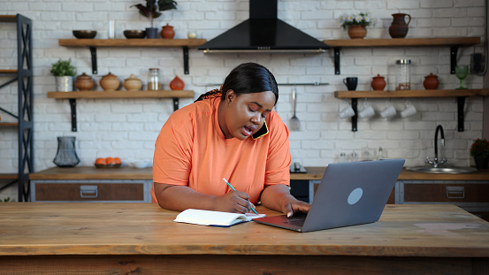 Plump woman holds phone between ear and shoulder takes notes