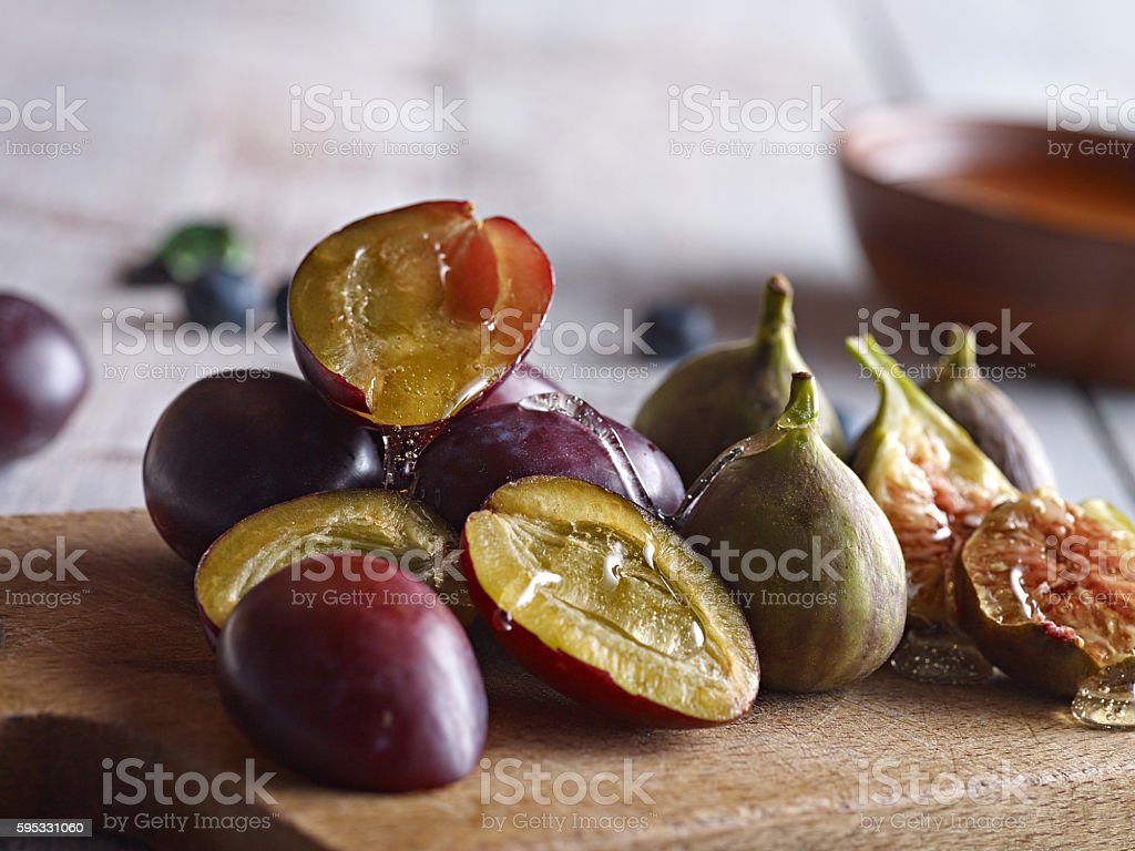 Plums and figs on wooden board served with honey stock photo