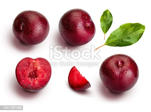 Plums from different angles and leaves isolated on white background. Appetizing and healthy red plums, whole and cut into segments with an aspect of illustration.
