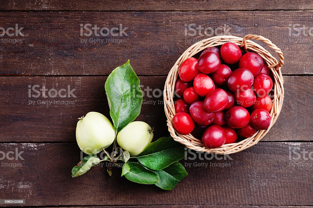 Plums in a basket and apples royalty-free stock photo