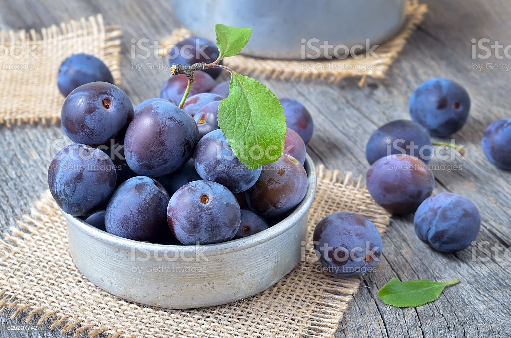 Plums in bowl on the wooden table stock photo