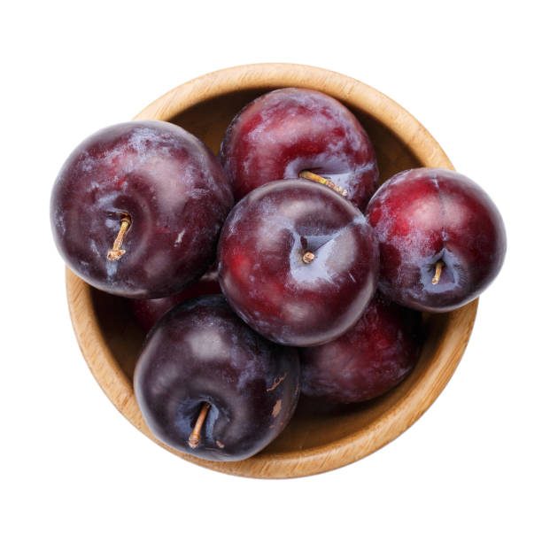 Plums in wooden bowl isolated on white background. Top view. stock photo