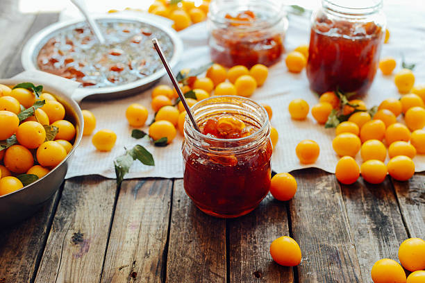 plums jam in a small cup. - mirabelle photos et images de collection