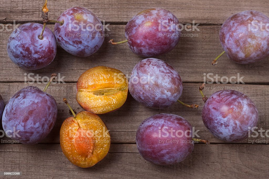 plums on the old wooden background stock photo