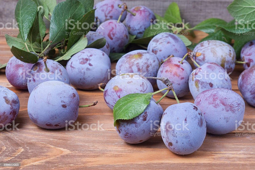 plums with leaves on the wooden background stock photo