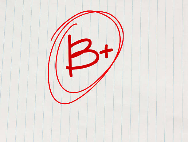 B plus (B+) grade written in red on notebook paper stock photo