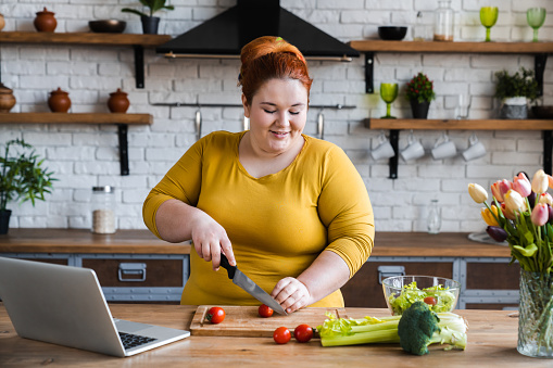Plus size , caucasian woman learning to make salad and healthy food from social media,Social distancing, stay at home concept