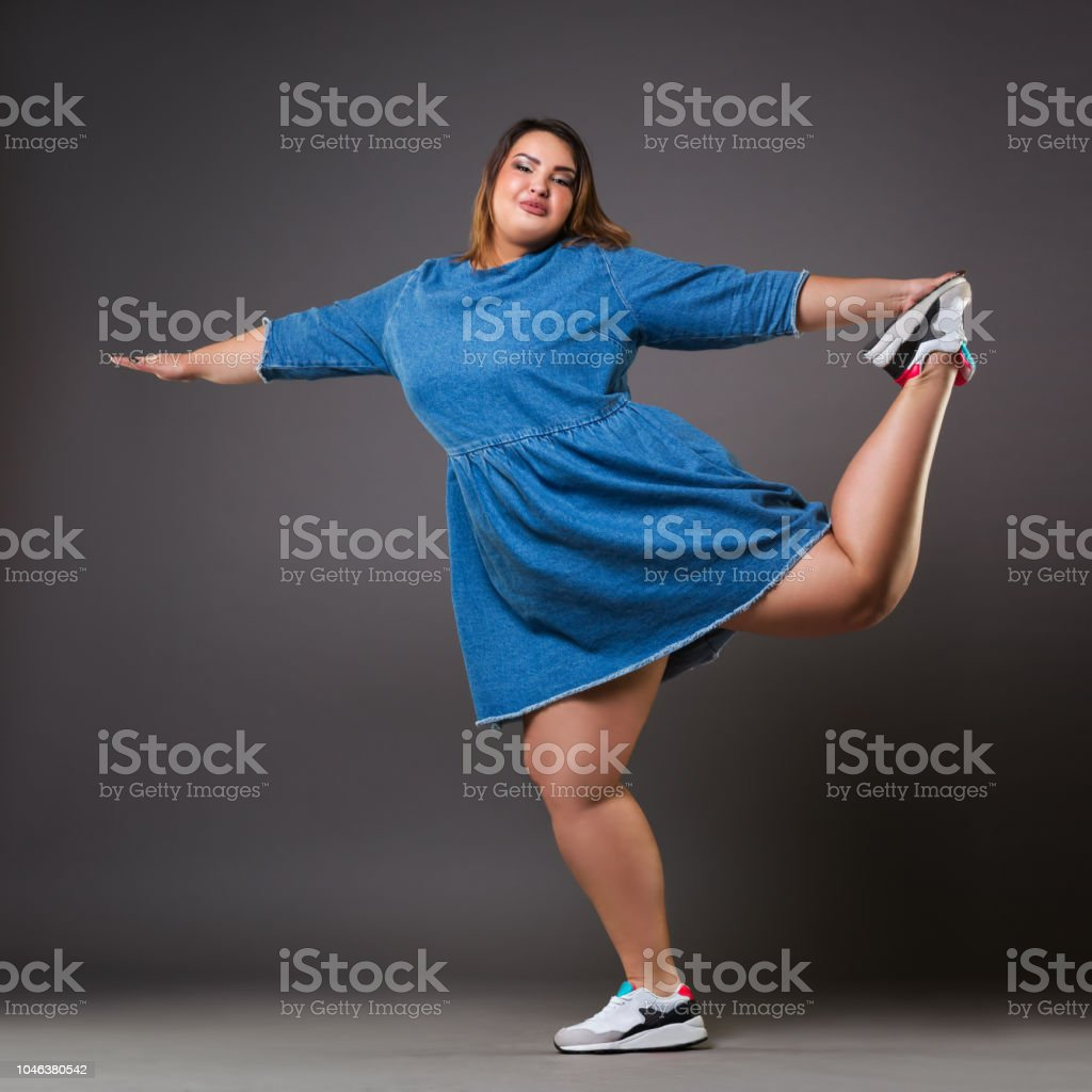 Plus size fashion model in casual clothes, fat woman on gray background, overweight female body stock photo