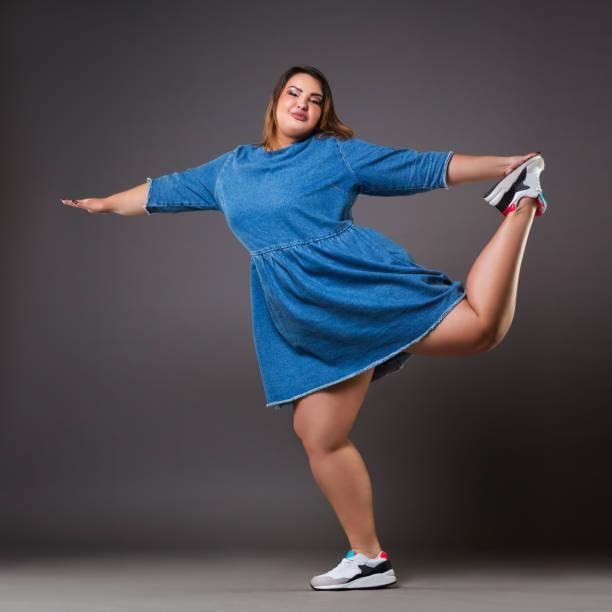 plus size mode-modell in alltagskleidung, fette frau auf grauem hintergrund übergewicht weiblichen körper - damen sporthose übergröße stock-fotos und bilder