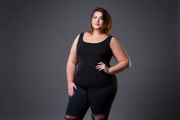 plus size mode-modell in alltagskleidung, fette frau auf grauem hintergrund übergewicht weiblichen körper - damen jeans übergrößen stock-fotos und bilder