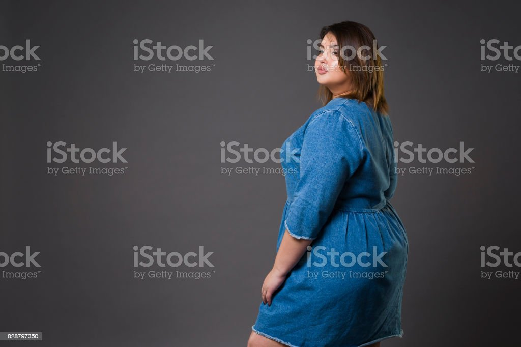 Plus size fashion model in casual jeans clothes, fat woman on gray background, overweight female body stock photo