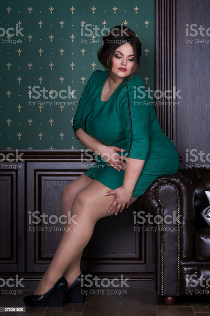 Plus size fashion model in green evening dress, fat woman on luxury interior, overweight female body stock photo