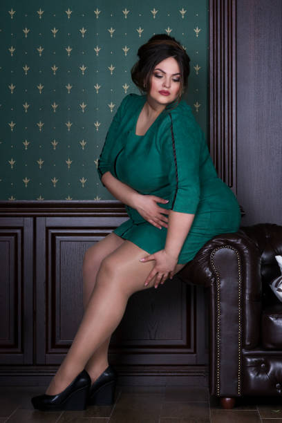 plus size fashion model in green evening dress, fat woman on luxury interior, overweight female body - curvy voluptuous women stock photos and pictures