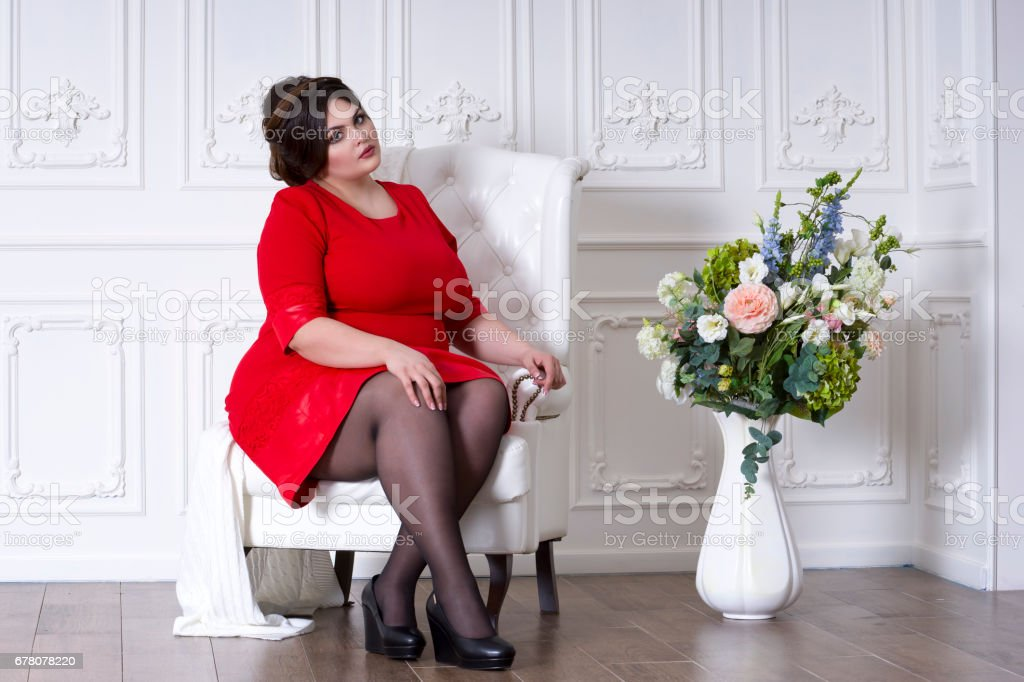 Plus size fashion model in red evening dress, fat woman on luxury interior, overweight female body stock photo