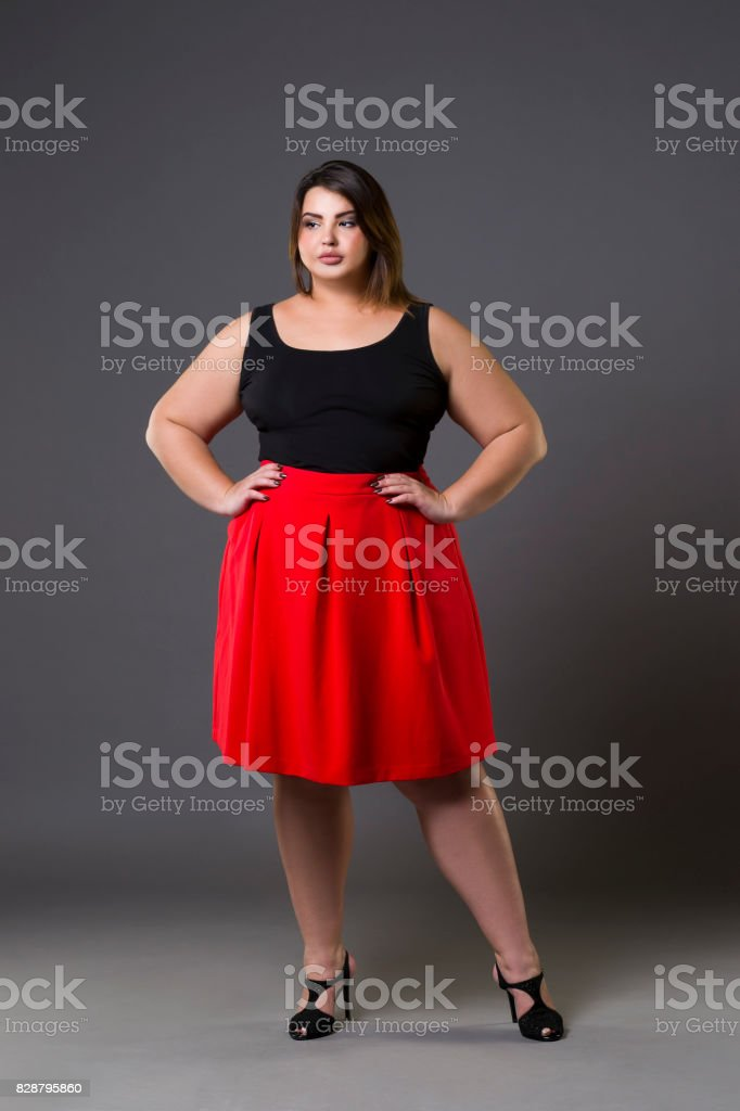 Plus size fashion model in red skirt, fat woman on gray background, overweight female body stock photo