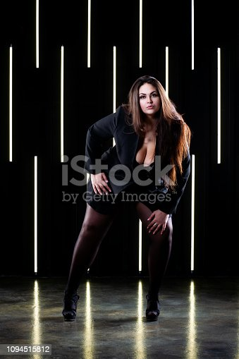 498310066istockphoto Plus size fashion model in sexy clothes, fat woman posing on the background of neon lamps 1094515812