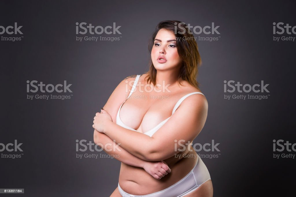 Plus size fashion model in underwear, young fat woman on gray background, overweight female body стоковое фото