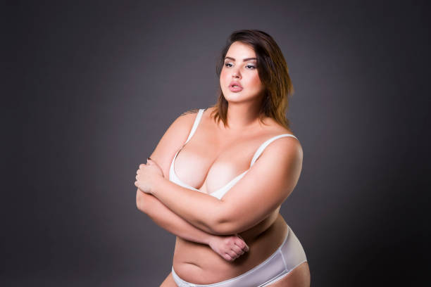 Cтоковое фото Plus size fashion model in underwear, young fat woman on gray background, overweight female body