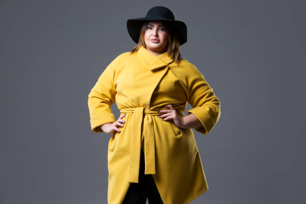 Plus size fashion model in yellow coat and black hat on gray background stock photo