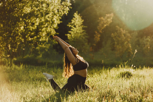 Plus size girl doing yoga in nature. Beautiful plus size girl doing yoga in nature on a sunny summer day. Body positive, sports for women, harmony, asana, healthy lifestyle, inspiring look, self-love and wellness. body positive stock pictures, royalty-free photos & images