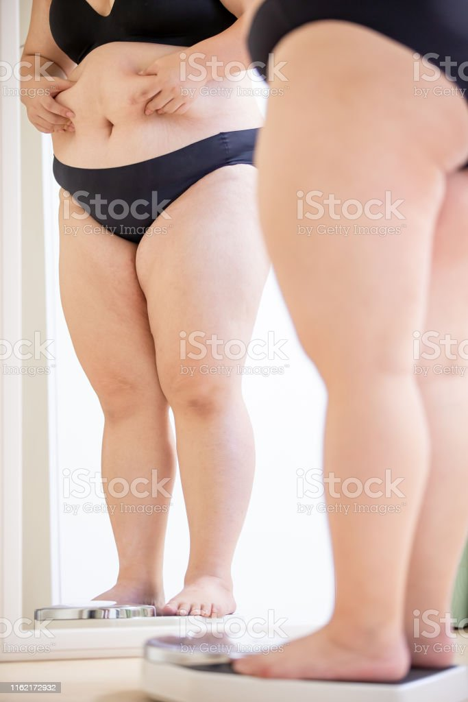 plus size asian girl look mirror and measure her weight by scale