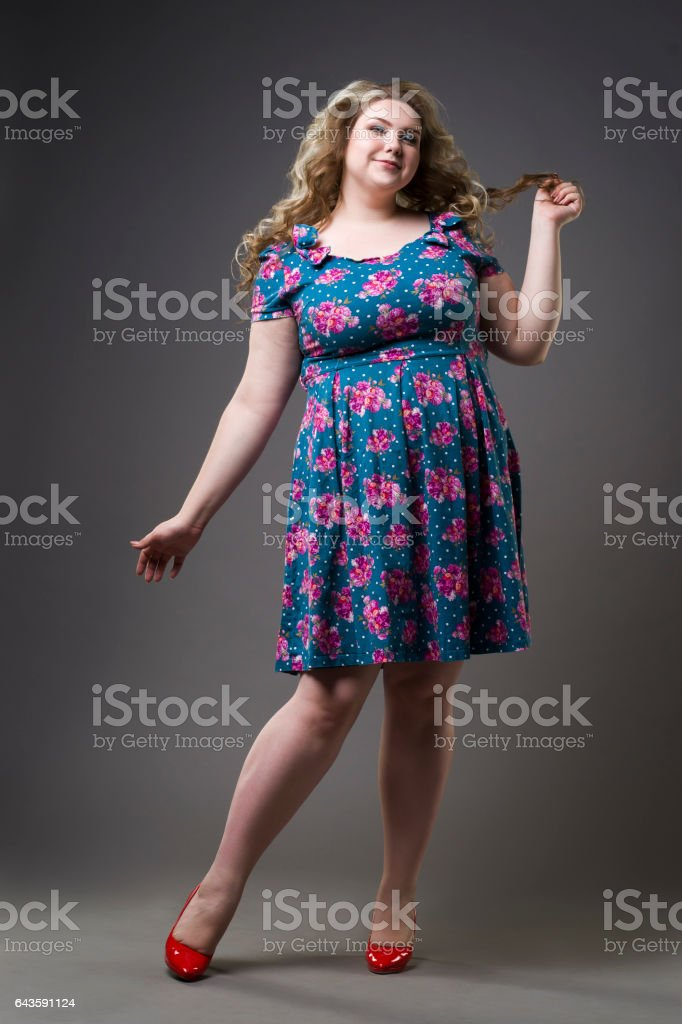 Plus size model in black dres on gray studio background stock photo