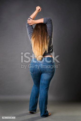 istock Plus size model in blue jeans, xxl woman on gray 626658368