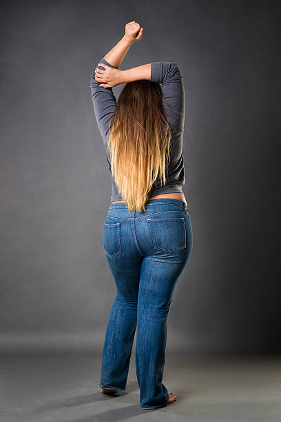 plus size model in blue jeans, xxl woman on gray - buttock stock photos and pictures