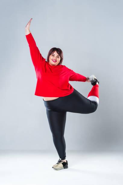 plus-size-model in der sportswear fette frau dabei training auf grauem hintergrund, gesunden lebensstil-konzept - damen leggings übergrößen stock-fotos und bilder