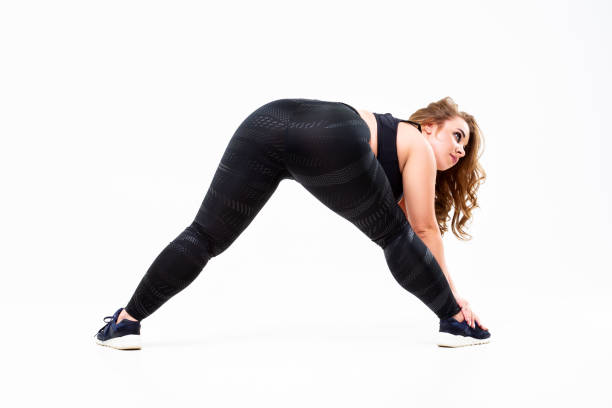 größen-modell in sportbekleidung, fette frau beim training auf weißem hintergrund, körperpositives konzept - damen leggings übergrößen stock-fotos und bilder