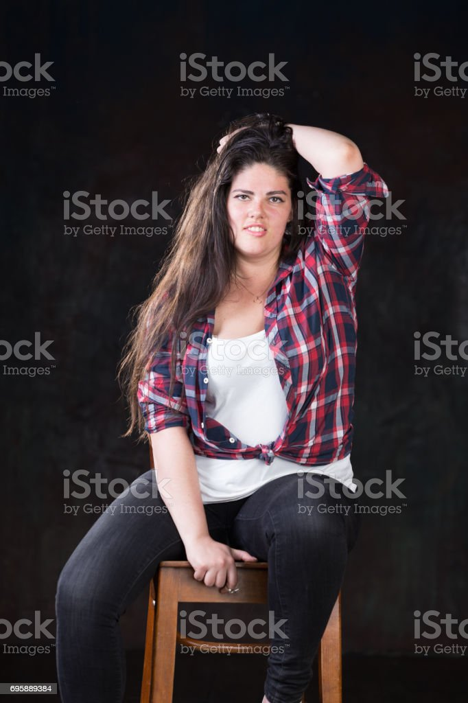Plus size model sitting on a chair in a casual style outfit. stock photo