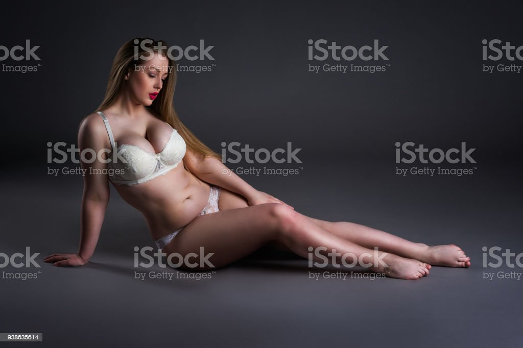 Plus size sexy model in white underwear, fat woman sitting on gray  background, overweight female body - Stock image .