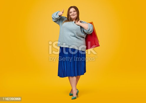 Pretty plump woman in elegant outfit holding paper bags and showing thumb up gesture while standing on bright yellow background