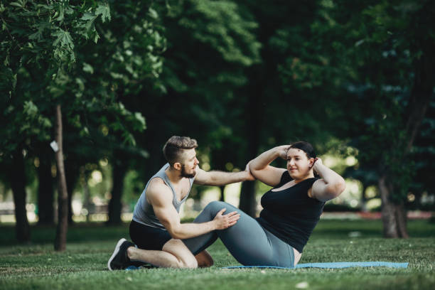 Plus size woman working out with personal trainer stock photo