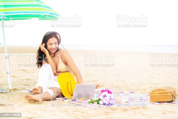 Plus size young woman sitting on the beach.